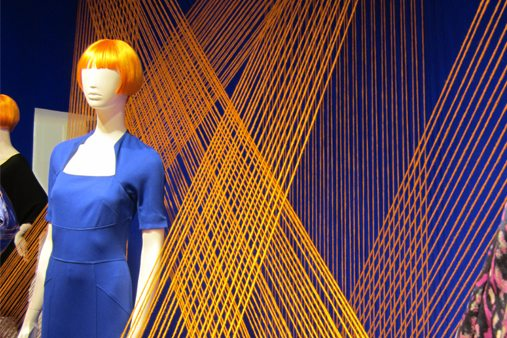 Close-up image of mannequins within the visual merchandising scheme, with orange wool forming a striking backdrop