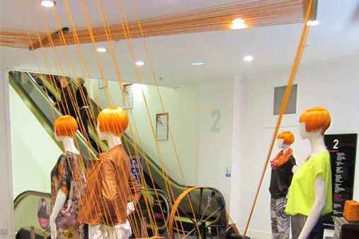 Prop Studios designed the visual merchandising scheme so that the wool would twist into the window and through the vintage machinery, forming a striking art installation