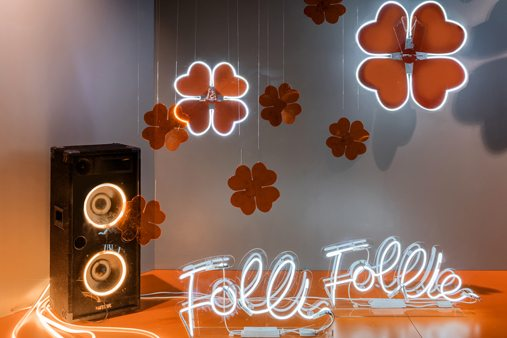Image of speaker and neon sign within Folli Follie display