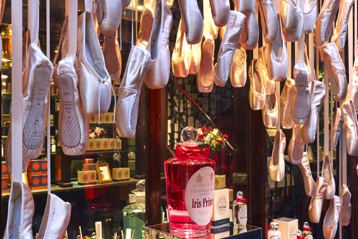 Close-up shot of Prop Studios' window display for Penhaligon's, highlighting the ballet shoes and perfume bottle on a silver mirror plinth