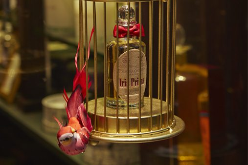 Close-up image of a bird cage designed by Prop Studios containing a bottle of Penhaligon's perfume