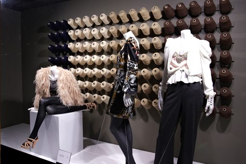 Alternate angle of House Of Fraser window display, showing mannequins against a backdrop of cotton spools