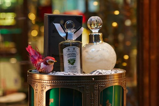 A display stand showcasing two Penhaligon's perfume bottles, alongside a small bird sculpture designed by Prop Studios