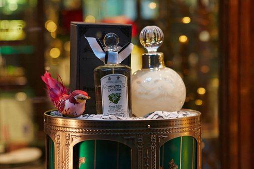 A display stand showcasing two Penhaligon's perfume bottles, alongside a small bird sculpture designed by Prop Studios